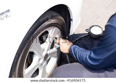 Man checking tire air pressure with gauge