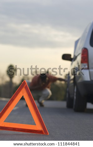 Man checking tire with warning triangle in foreground - stock photo