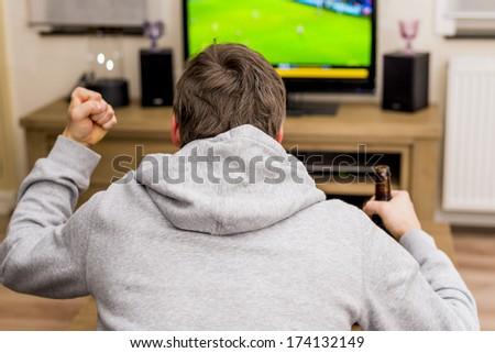 man cheering for soccer goal on tv - stock photo