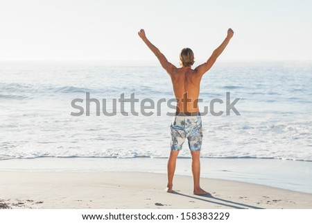 Man cheering looking out to the sea on beach on a sunny day - stock photo