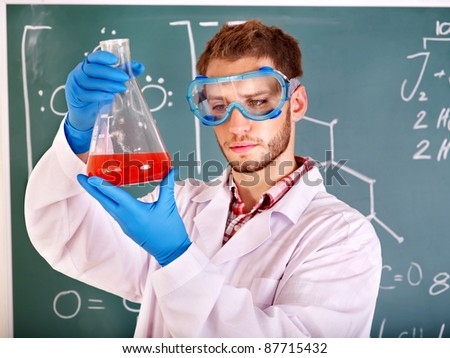 Man chemistry student with flask in classroom. - stock photo