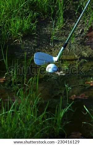Man chipping ball from water hazard - stock photo