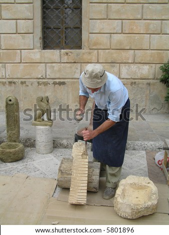 man chiseling stone sculpture - stock photo