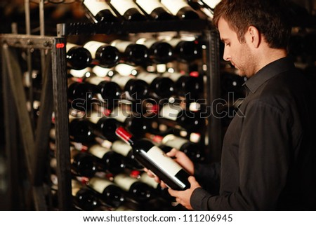 Man chooses a bottle of wine - stock photo