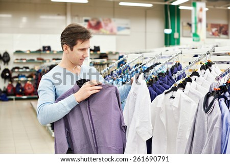 Man chooses a shirt in the store - stock photo