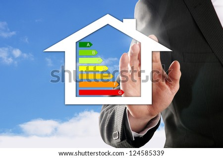 man chooses his energy-efficient dream house in front of the blue sky - stock photo