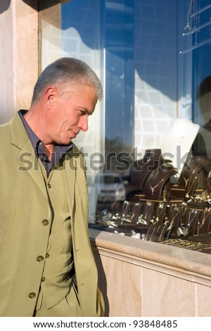 man chooses jewelry to showcase - stock photo