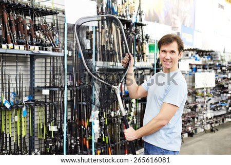 Man chooses landing net for fishing in the sports shop - stock photo