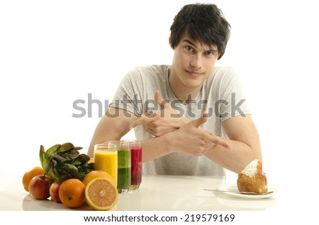 Man choosing between fruits, smoothie and organic healthy food against sweets, sugar, lots of candies - stock photo