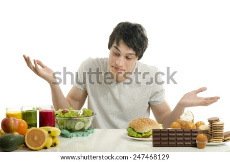 Man choosing between fruits, smoothie and organic healthy food against sweets, sugar, lots of candies and a big hamburger, fast food - stock photo