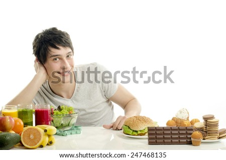 Man choosing between fruits, smoothie and organic healthy food against sweets, sugar, lots of candies and a big hamburger, fast food