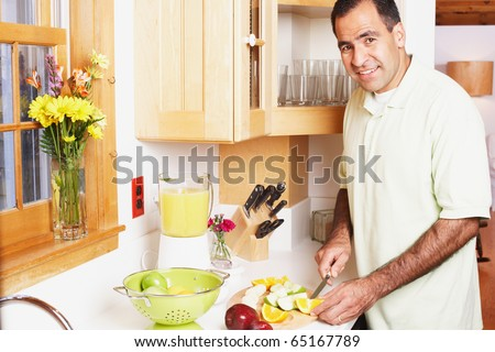 Man chopping fruit in the kitchen - stock photo