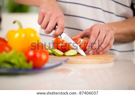 man chops vegetables for a salad