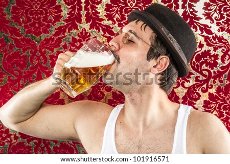 Man chugging frothy light beer on his own from large glass mug in hat, glasses, white tank top, red gold fancy background at bar retro style