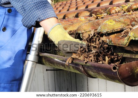 Man Cleaning a rain gutter in Close up - stock photo
