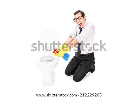 Man cleaning a toilet with disinfecting spray isolated on white background - stock photo