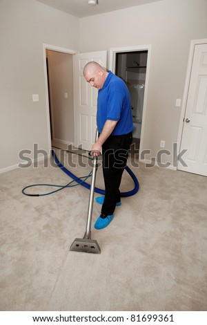 Man cleaning carpet with commercial cleaning equipment - stock photo