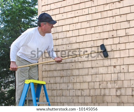Man cleaning cedar shingles - stock photo