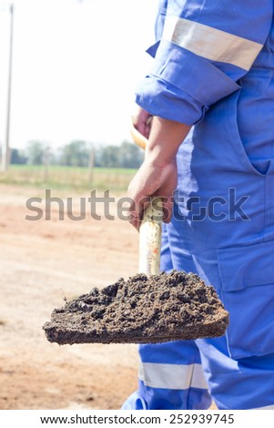 man cleaning crude oil contaminated by shovel - stock photo
