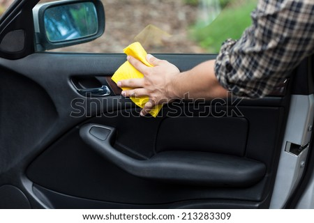 Man cleaning door in a car, horizontal - stock photo