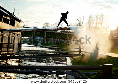Man cleaning floating restaurant - stock photo