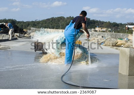 Man cleaning nets - stock photo