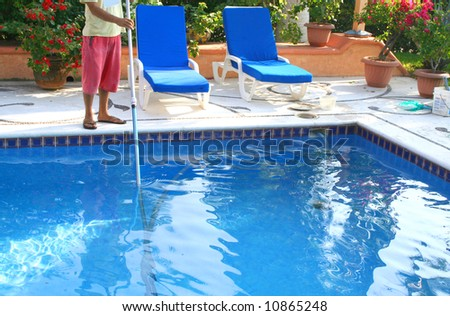 man cleaning pool with large pole and lots of flowers - stock photo
