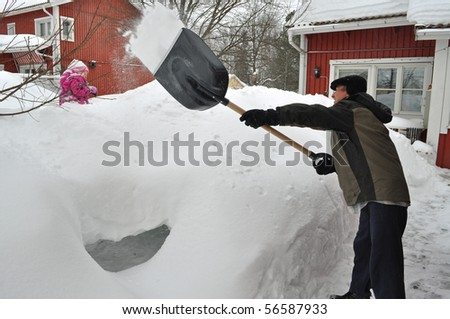 man cleaning snow near the house - stock photo