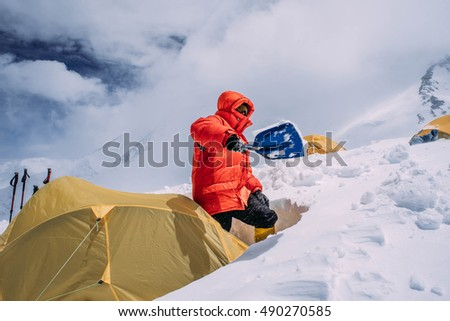 man cleaning tent of snow in mountains