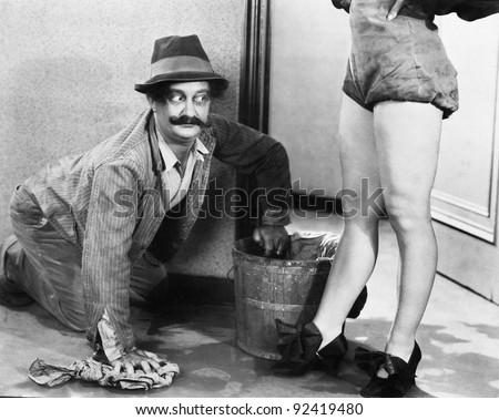 Man cleaning the floor looking at the legs of a woman - stock photo