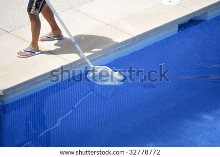 Man cleaning the swimming pool. Summer work - stock photo