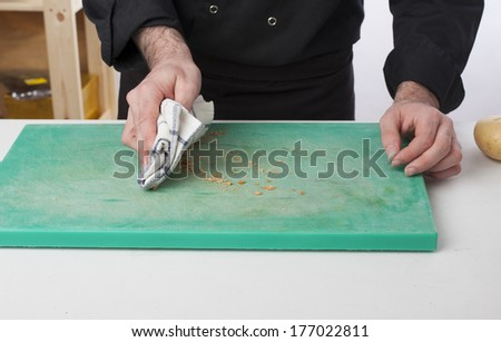 Man cleaning the table in a kitchen. - stock photo