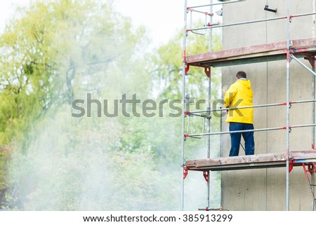 Man cleaning wall. Scaffolding, construction site in progress. Building renovation. Cleaning dirtiness.