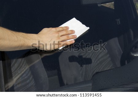 Man cleaning windscreen on a sunny day. - stock photo