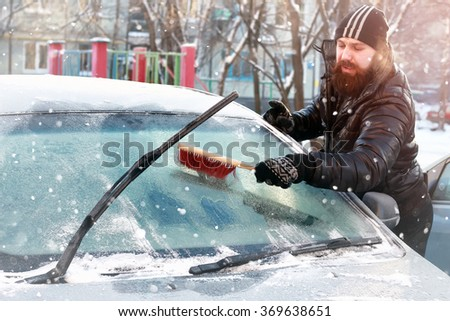 man cleans snow from the glass at the car