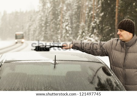 Man cleans the car out of the snow in snow storm - stock photo