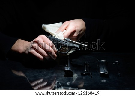 man cleans the disassembled gun on dark background