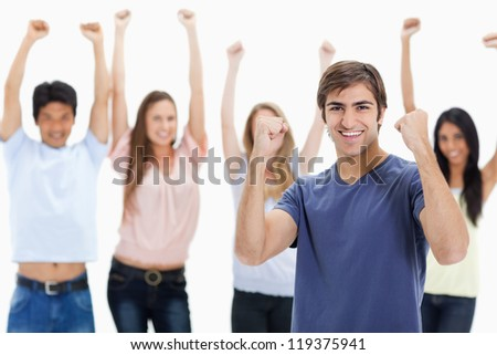 Man clenching his fists with people behind him raising their arms against white background - stock photo