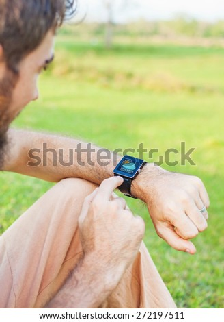 Man clicking on his smart watch showing a weather app - stock photo