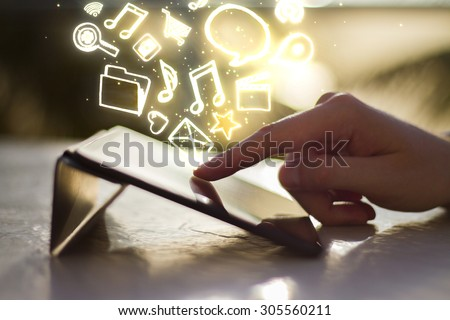 man clicks on digital tablet at sunrise, with social media icons - stock photo