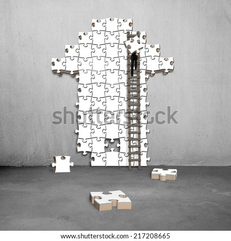 man climb ladder for arrow shape puzzle on concrete wall - stock photo