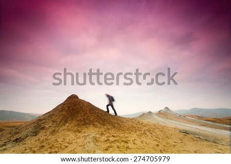 Man climbing a hill with colorful clouds