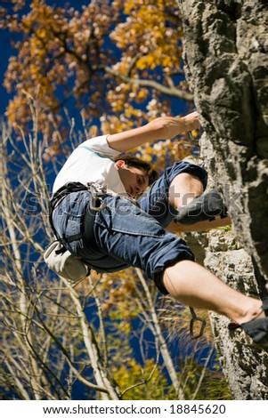 Man climbing a rock at a perfect clear autumn day - stock photo