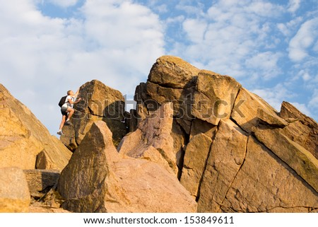 Man climbing a rocky mountain peak wearing a backpack enjoying an active summer vacation in nature