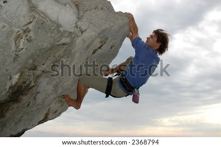Man climbing a steep rock with overhang - stock photo