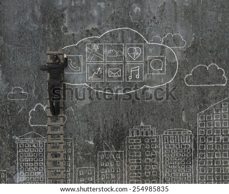 Man climbing and drawing cloud app icons doodles on mottled wall background - stock photo