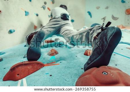 Man climbing artificial boulder indoors, view from below - stock photo