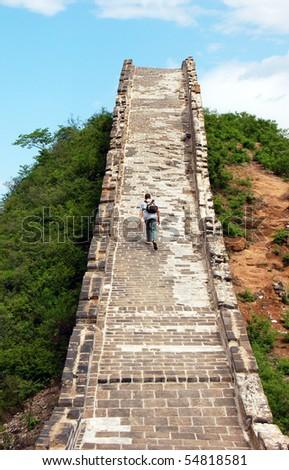 Man climbing Great Wall of China - stock photo