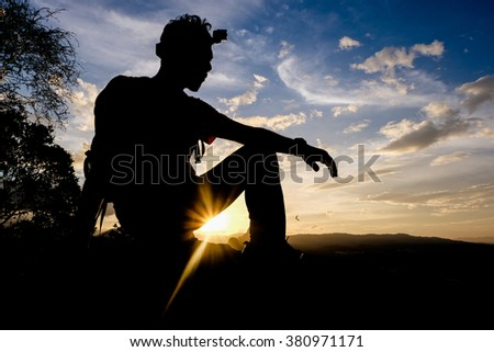 Man climbing hiking exploring accomplish silhouette in mountains. - stock photo