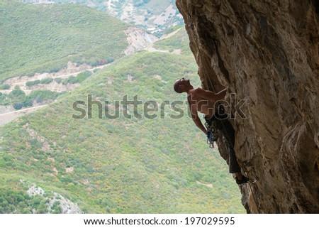 Man climbing in a canyon in Buggerru, Sardinia, Italy - stock photo